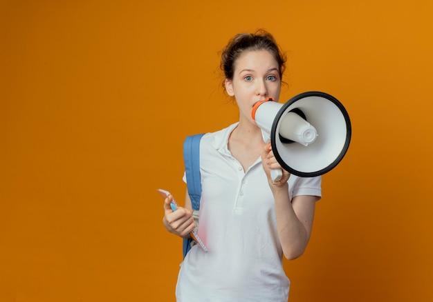 Beeindruckte junge hübsche studentin, die rückentasche hält, die stift und notizblock hält, der durch sprecher lokalisiert auf orange hintergrund mit kopienraum spricht