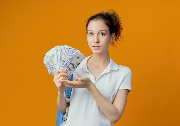 Beeindruckte junge hübsche studentin, die rückentasche hält und mit der hand auf geld zeigt, das auf orange hintergrund mit kopienraum lokalisiert ist