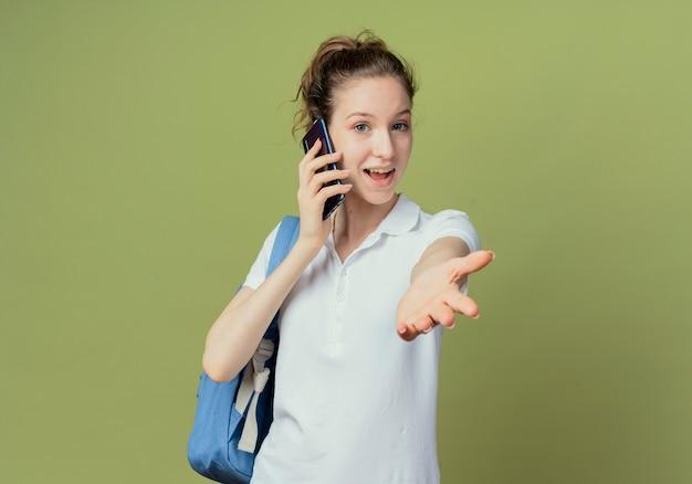 Beeindruckte junge hübsche studentin, die rückentasche trägt, die am telefon spricht und hand an kamera lokalisiert auf grünem hintergrund mit kopienraum ausdehnt
