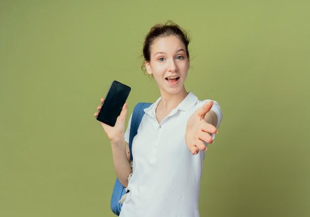 Beeindruckte junge hübsche studentin mit rückentasche, die handy hält und die hand ausstreckt