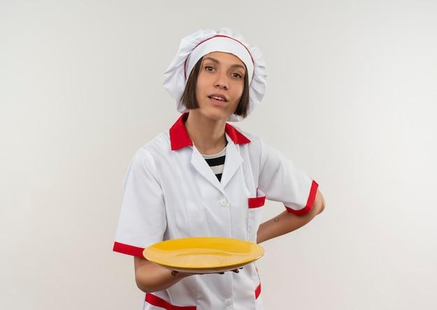 Beeindruckte junge köchin in der kochuniform, die platte mit hand auf taille hält, lokalisiert auf weiß mit kopienraum