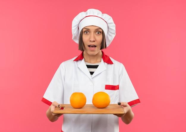 Beeindruckte junge köchin in der kochuniform, die schneidebrett mit orangen auf lokalisiertem rosa mit kopienraum hält