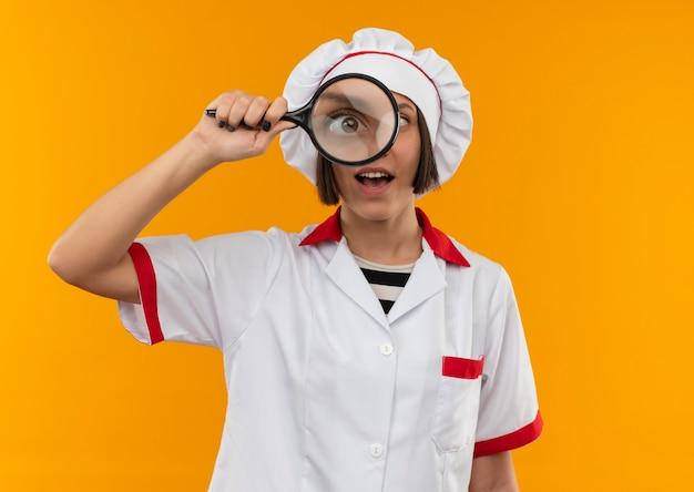 Beeindruckte junge köchin in kochuniform, die durch lupe lokalisiert auf orange schaut
