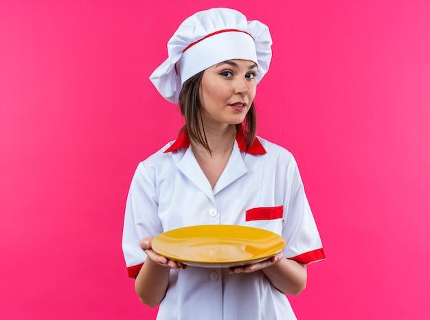 Beeindruckte junge köchin in kochuniform mit teller isoliert auf rosa hintergrund