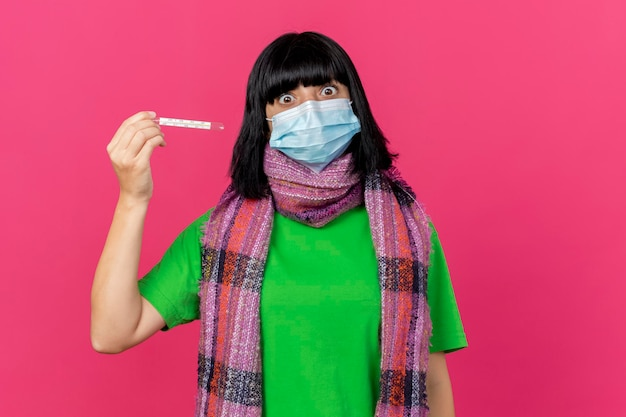 Beeindruckte junge kranke frau, die maske und schal hält, die thermometer horizontal betrachten, das vorne auf rosa wand mit kopienraum lokalisiert betrachtet