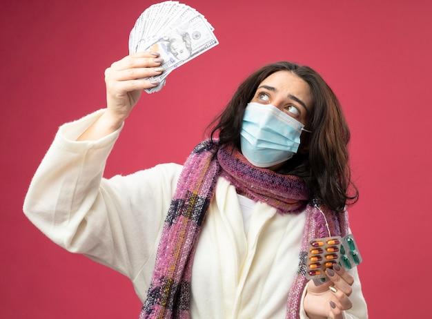 Beeindruckte junge kranke frau, die robe und schal mit maske hält, die geld und packungen von medizinischen kapseln hält, die anheben und geld betrachten, das auf rosa wand lokalisiert wird