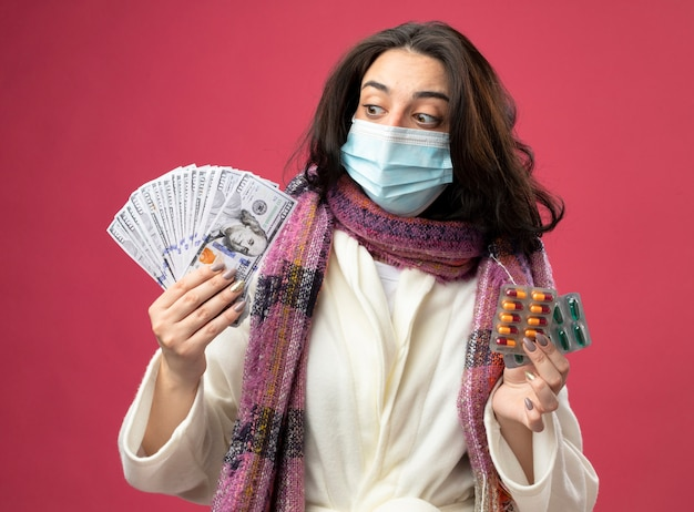 Beeindruckte junge kranke frau, die robe und schal mit maske hält, die geld und packungen von medizinischen kapseln hält, die geld lokalisiert auf rosa wand betrachten