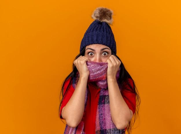 Beeindruckte junge kranke frau, die wintermütze und schal trägt, die frontabdeckungsmund mit schal lokalisiert auf orange wand betrachten
