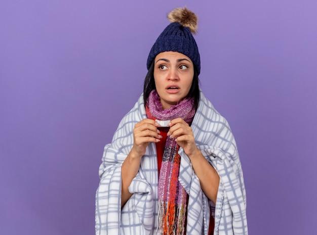 Beeindruckte junge kranke frau, die wintermütze und schal trägt, eingewickelt in plaid, das medizinischen gips hält, der seite lokalisiert auf lila wand betrachtet