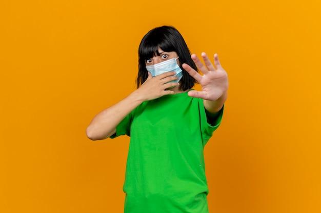 Beeindruckte junge kranke frau mit maske, die das gesicht berührt, streckt die hand nach vorne aus und betrachtet die front lokalisiert auf der orangefarbenen wand