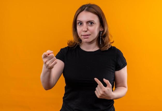 Beeindruckte junge lässige frau, die auf isolierten orangefarbenen raum mit kopierraum zeigt und sich selbst zeigt