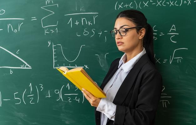 Beeindruckte junge lehrerin mit brille, die im klassenzimmer vor der tafel steht und ein buch liest