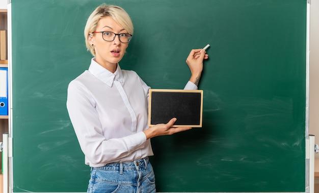 Beeindruckte junge lehrerin mit brille im klassenzimmer, die in der profilansicht vor der tafel steht