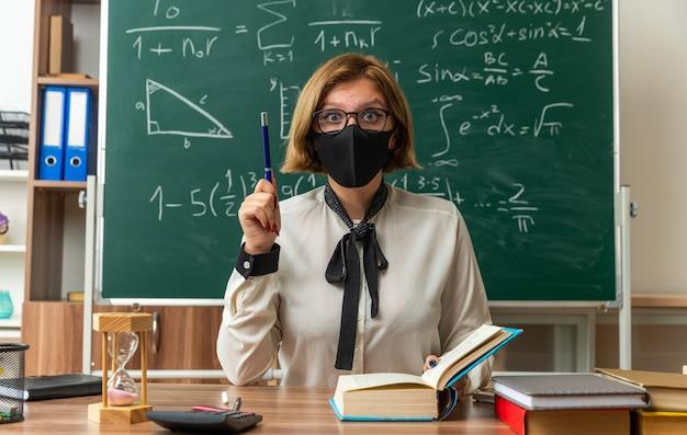 Beeindruckte junge lehrerin mit brille und medizinischer maske sitzt am tisch mit schulwerkzeugen, die einen stift im klassenzimmer halten