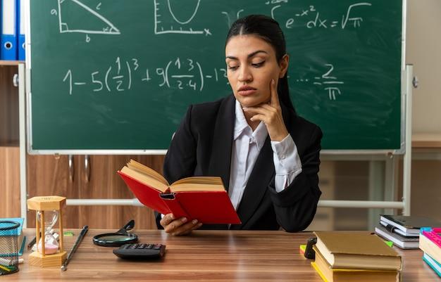 Beeindruckte junge lehrerin sitzt am tisch mit schulmaterial und liest buch und legt den finger auf die wange im klassenzimmer