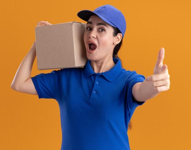 Beeindruckte junge lieferfrau in uniform und mütze, die karton auf der schulter hält und daumen nach oben isoliert auf oranger wand zeigt