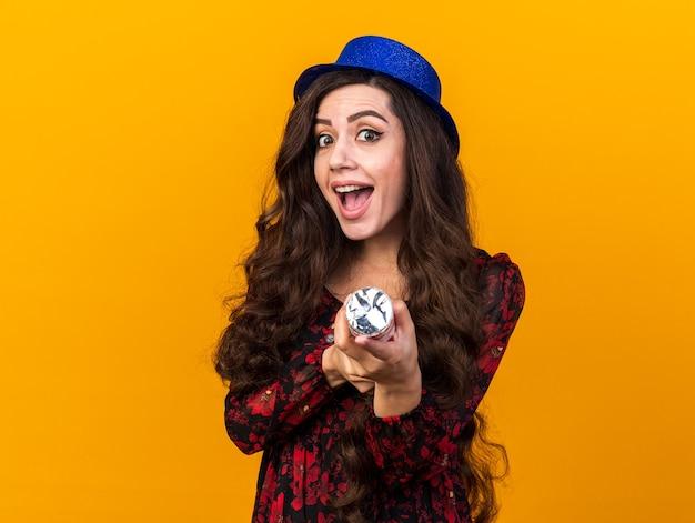 Beeindruckte junge partyfrau mit partyhut, die konfettikanone hält und auf die vorderseite isoliert auf orangefarbener wand zeigt
