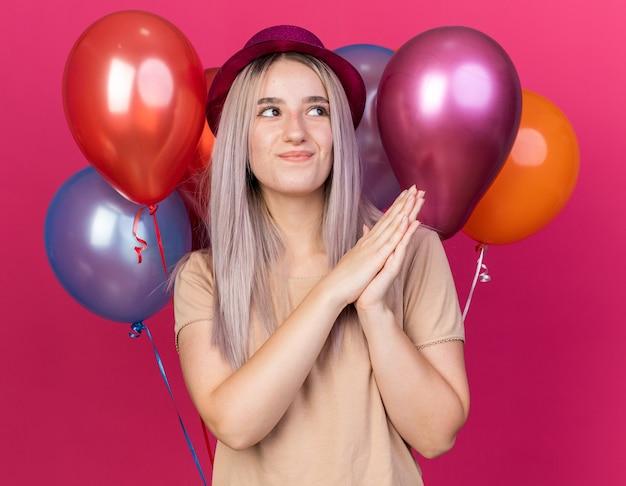 Beeindruckte junge schöne frau mit partyhut, die vor ballons steht und die hände zusammenhält, isoliert auf rosa wand