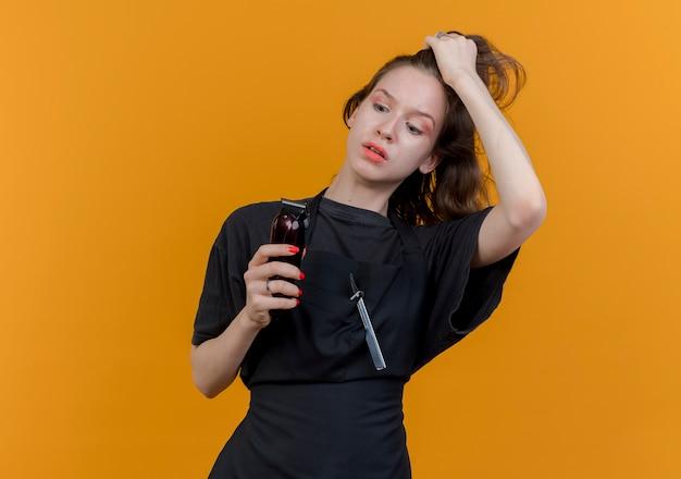 Beeindruckte junge slawische friseurin, die uniform hält, die haarschneidemaschinen hält und betrachtet und haare isoliert auf orangefarbenem hintergrund mit kopienraum zieht