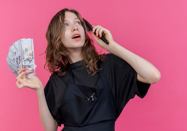 Beeindruckte junge slawische friseurin, die uniform mit kamm und geld trägt