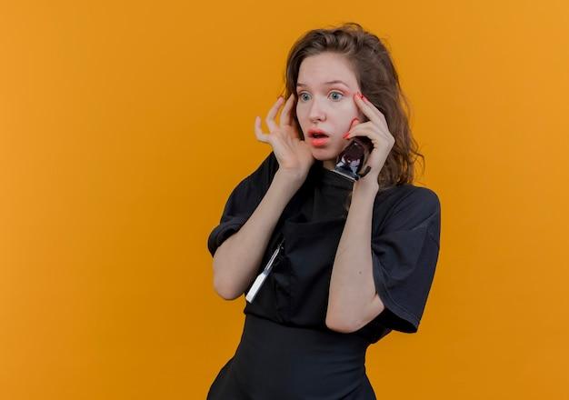 Beeindruckte junge slawische friseurin in uniform, die gerade haarschneidemaschinen hält und das gesicht berührt
