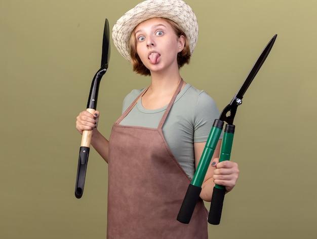 Beeindruckte junge slawische gärtnerin, die einen gartenhut trägt, steckt die zunge heraus und hält den spaten und die gartenschere auf olivgrün