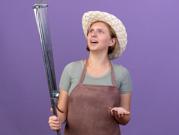 Beeindruckte junge slawische gärtnerin mit gartenhut, die blattrechen hält und betrachtet