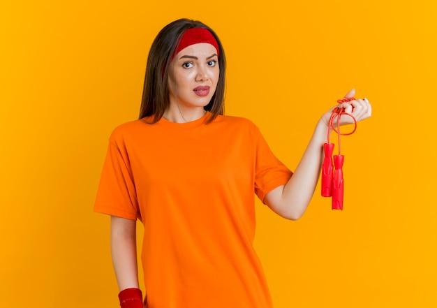 Beeindruckte junge sportliche frau, die stirnband und armbänder hält, die springseil suchen