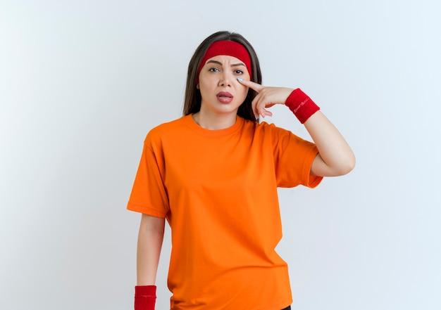 Beeindruckte junge sportliche frau, die stirnband und armbänder trägt, die augendeckel abziehen, lokalisiert auf weißer wand mit kopienraum