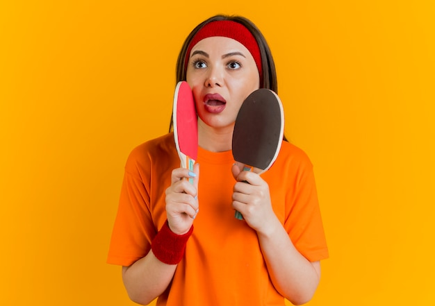 Beeindruckte junge sportliche frau, die stirnband und armbänder trägt, die tischtennisschläger halten, die gesicht mit ihnen betrachten, die seite betrachten