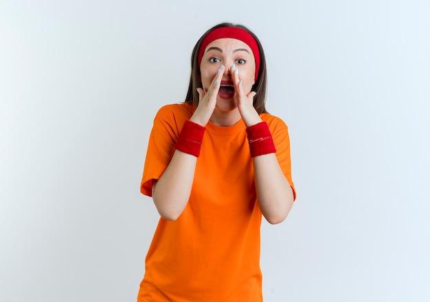 Beeindruckte junge sportliche frau, die stirnband und armbänder trägt und isoliert flüstert