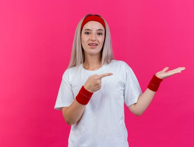 Beeindruckte junge sportliche frau mit zahnspangen, die stirnband und armbänder tragen, zeigt auf leere hand lokalisiert auf rosa wand