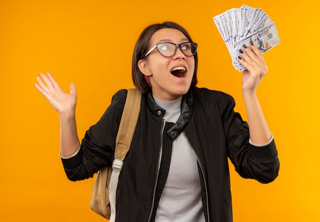 Beeindruckte junge studentin, die brille und rückentasche hält, die geld auf orange isoliert und betrachtet
