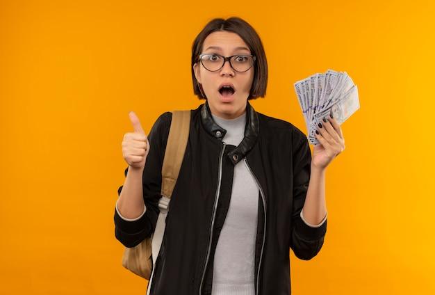 Beeindruckte junge studentin, die brille und rückentasche hält, die geld hält, das daumen auf orange lokalisiert zeigt