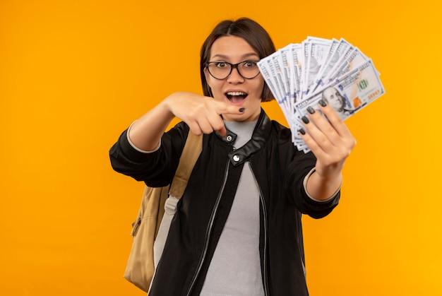 Beeindruckte junge studentin, die brille und rückentasche hält und auf geld zeigt, das auf orange isoliert ist