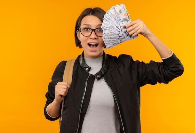 Beeindruckte junge studentin, die brille und rückentasche trägt, die geld lokalisiert auf orange hält