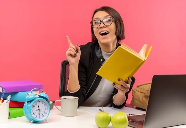 Beeindruckte junge studentin, die eine brille trägt, die am schreibtisch hält buch hält, das hausaufgaben macht, die finger lokalisiert auf rosa
