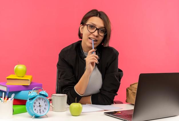 Beeindruckte junge studentin, die eine brille trägt, die am schreibtisch sitzt und stift auf lippe isoliert auf rosa setzt