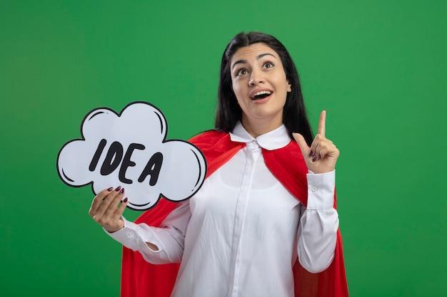 Beeindruckte junge superfrau, die ideenblase hält und nach realer idee sucht, die lokal auf grüner wand sucht