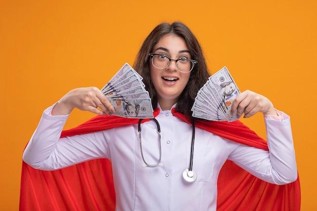 Beeindruckte junge superheldin in arztuniform und stethoskop mit brille, die geld hält und auf die vorderseite isoliert an der wand schaut
