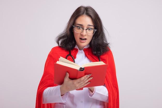 Beeindruckte junge superheldin in rotem umhang mit arztuniform und stethoskop, die ein buch isoliert auf weißer wand mit kopierraum hält und liest