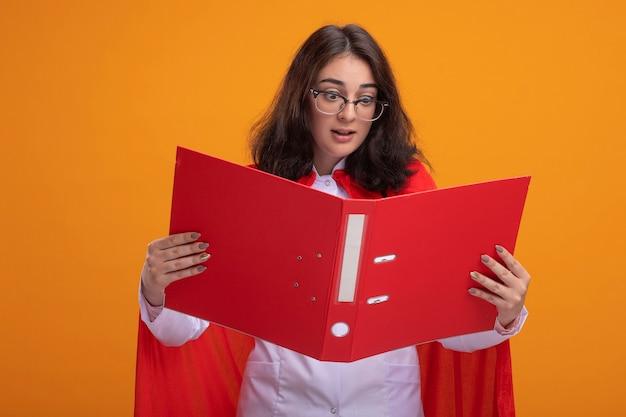 Beeindruckte junge superheldin in rotem umhang mit arztuniform und stethoskop mit brille, die den ordner isoliert auf oranger wand hält und betrachtet