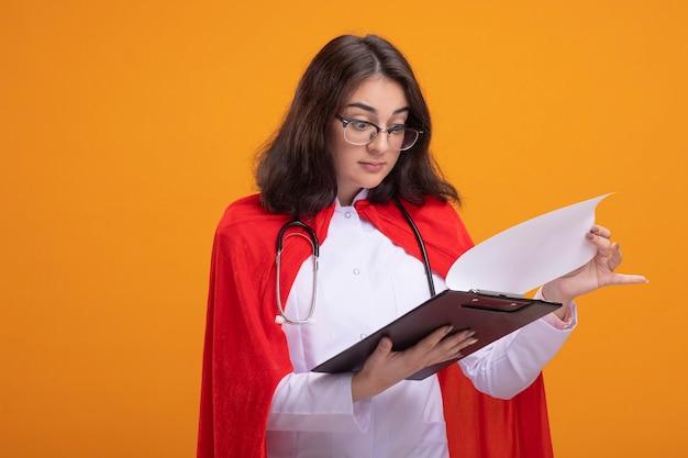 Beeindruckte junge superheldin in rotem umhang mit arztuniform und stethoskop mit brille, die die zwischenablage isoliert auf oranger wand mit kopierraum hält und betrachtet