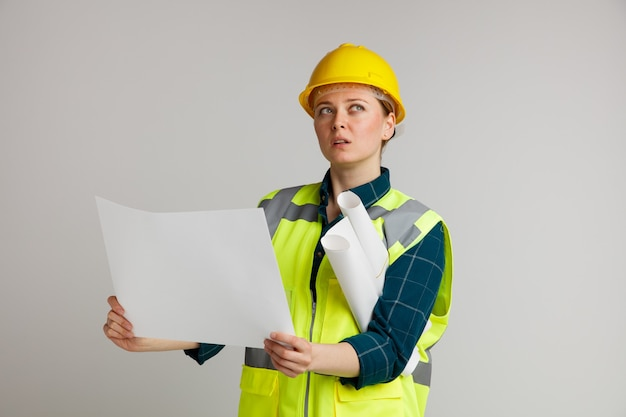 Beeindruckte junge weibliche bauarbeiterin, die schutzhelm und sicherheitsweste hält, die papier und andere unter dem arm halten und nach oben schauen