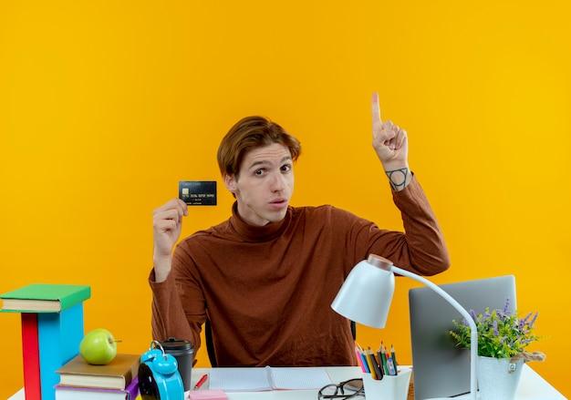 Beeindruckte jungen studentenjungen, der am schreibtisch mit schulwerkzeugen sitzt, die kreditkarte und punkte nach oben halten