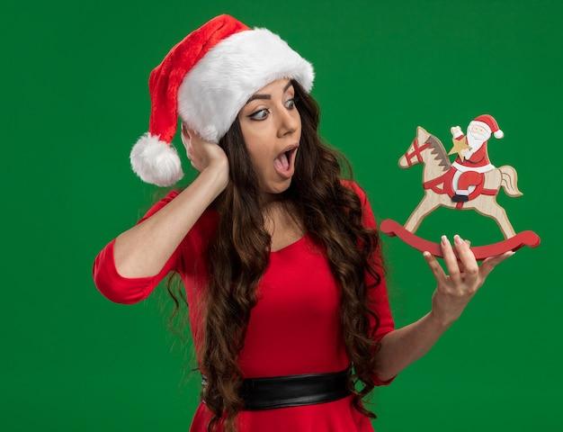 Beeindruckte junges hübsches mädchen, das weihnachtsmütze hält, die weihnachtsmann auf schaukelpferdefigur hält, die es betrachtet, hand auf kopf lokalisiert auf grünem hintergrund hält
