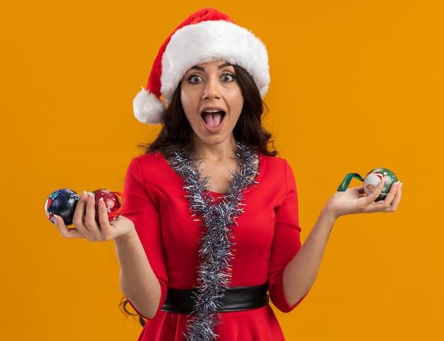 Beeindruckte junges hübsches mädchen, das weihnachtsmütze und lametta-girlande um den hals trägt, der weihnachtskugeln hält, die kamera lokalisiert auf orange hintergrund betrachten