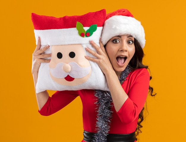 Beeindruckte junges hübsches mädchen, das weihnachtsmütze und lametta-girlande um den hals trägt, der weihnachtsmann-kissen-berührenden kopf mit ihm betrachtet kamera auf orange hintergrund lokalisiert