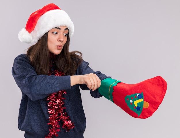Beeindruckte junges kaukasisches mädchen mit weihnachtsmütze und girlande um den hals steckt ihre hand in weihnachtsstrumpf lokalisiert auf weißem hintergrund mit kopienraum