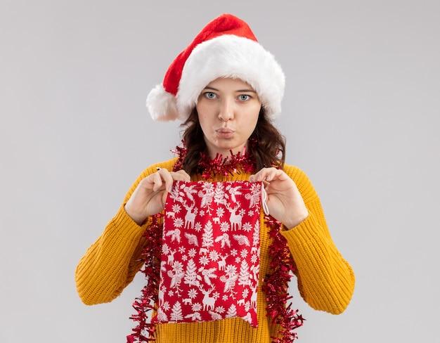 Beeindruckte junges slawisches mädchen mit weihnachtsmütze und mit girlande um hals, die weihnachtsgeschenktüte lokalisiert auf weißem hintergrund mit kopienraum hält